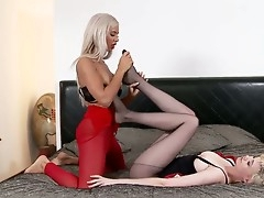 Shannon Reid and Ashley Bulgari are up for some foot fun as they relaxes on a soft bed. Shannon wears black pantyhose and Ashley has red stockings. After thorough foreplay they divulge into passionate play.